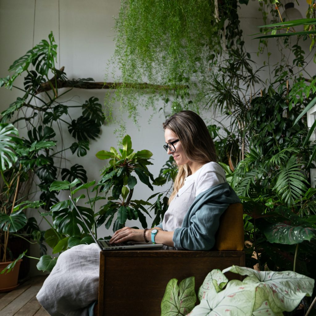 smiling woman gardener sitting on chair at cozy home garden, using laptop and talking in video chat